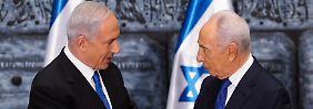 Netanjahu (l.) bekannt von Peres (r.) den Auftrag, aus einer Gruppe gegensätzlicher Parteien eine Regierung zu bilden.