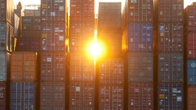 Die Sonne bricht sich durch Container am Hamburger Hafen Bahn. Auch in der Wirtschaft hellt sich die Lage spürbar auf.
