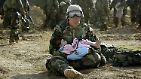 Bilder wie dieses gehen um die Welt und zeigen den Irrsinn der Operation: Ein US-Soldat hält ein irakisches Mädchen in den Armen, dessen Familie im Kreuzfeuer der beiden Kriegsgegner ums Leben gekommen ist.