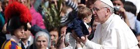 Papst Franziskus küsst während der Palmsonntagszeremonie ein Kind.