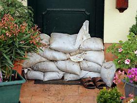 Sandsäcke vor einer Haustür: Wer noch kann, sollte Möbel und Geräte wegschaffen oder in sichere Räume in höheren Stockwerken bringen.