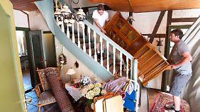 Helfer tragen in Hitzacker Möbel in ein höheres Stockwerk, damit diese nicht nass werden.
