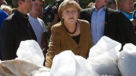 Kanzlerin Merkel blickt bei Bitterfeld über eine Barriere aus Sandsäcken.