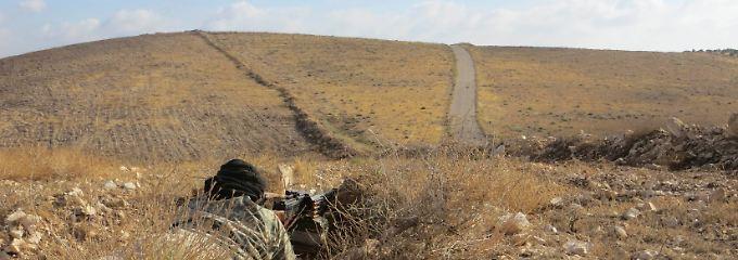 """Friedliche Hügel in einer uralten Landschaft: Im Gestrüpp hat ein Kämpfer der """"Freien Syrischen Armee"""" mit seinem schweren Maschinengewehr Stellung bezogen - der Konflikt droht sich auszuweiten."""