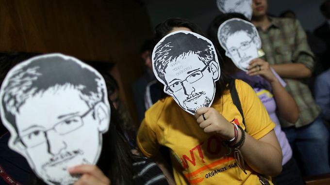 Für die einen Held, für die anderen Verräter: Aktivisten mit Snowden-Masken in Brasilien.