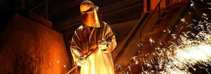 Ein Arbeiter entnimmt im ThyssenKrupp-Stahlwerk in Duisburg an eine Stahlprobe.