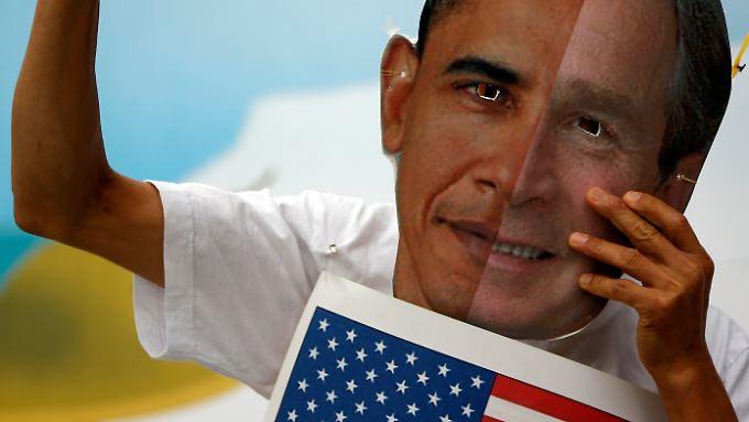 Ein Anti-Kriegs-Aktivist demonstriert mit Masken von US-Präsident Obama und Ex-Präsident Bush.