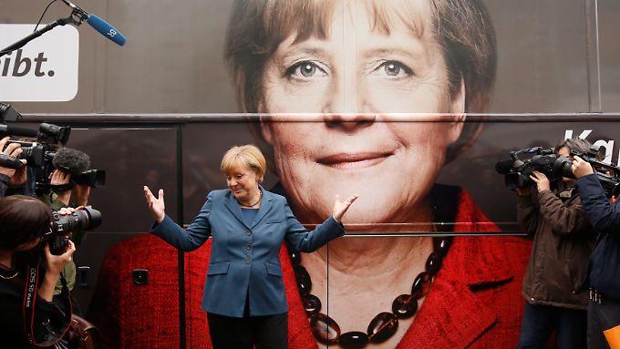 Angela Merkel scheint selbst davon überrascht, wie sie von ihren Wahlkämpfern inszeniert wird.