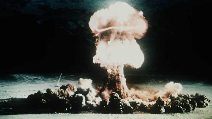 Ein Atompilz steigt nach der Explosion einer Atombombe über dem Testgelände in der Wüste von Nevada auf.