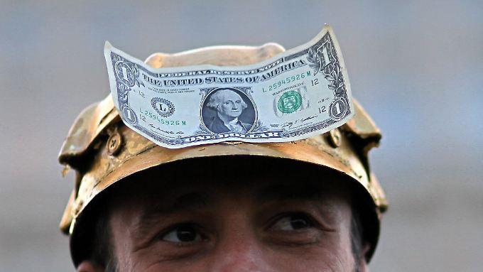 Ein Rumäne, der mit einem goldenen Helmauf dem Kopf mit einer Dollar-Note daran gegen das Goldminen-Projekt demonstriert.