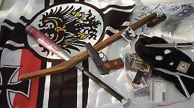 Diverse Waffen, Propagandamaterial und Reichskriegsflagge wurden 1994 in Brandenburg bei einer Polizei-Razzia gegen eine verbotene Versammlung einer rechtsextremen Gruppe sichergestellt.