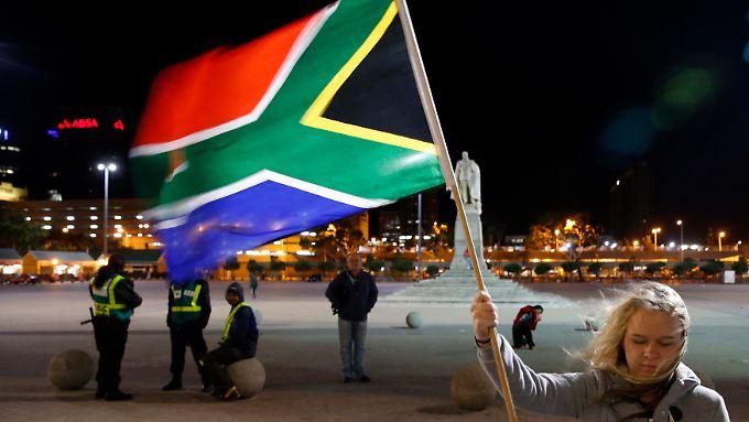 Eine Frau trauert in Kapstadt mit der Fahne Südafrikas um Nelson Mandela.