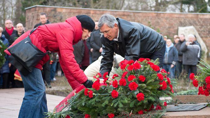 Katja Kipping und Bernd Riexinger legen einen Kranz an den Gräbern von Rosa Luxemburg und Karl Liebknecht nieder.