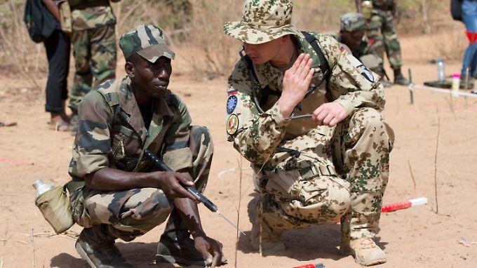 Ein deutscher Soldat bildet im Mai 2013 in Mali einen Pionier der malischen Armee bei der Minensuche aus.