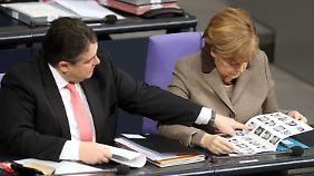"""Guck' mal: Gabriel und Merkel blättern im """"Kürschner"""", dem Handbuch, das alle Abgeordneten auflistet."""
