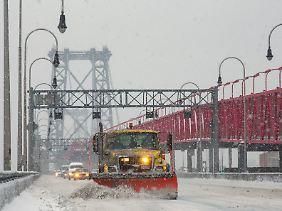 Schnee und Eis behindern seit Wochen den Verkehr: Ein Schneepflug kratzt über das frische Eis auf der Williamsburg-Bridge zwischen Brooklyn und Manhattan.