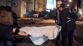 Demonstranten bringen Verletzte in Sicherheit.