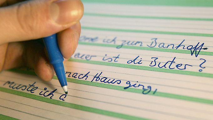 Ein Analphabet schreibt Sätze zur Übung in ein Schulheft.