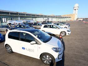 """Elektrisch angetriebene Testwagen warten in der Berliner Frühjahrssonne auf neugierige Fahrer: Auf dem Tempelhofer Feld lädt Volkswagen zu """"E-Mobilitätswochen""""."""