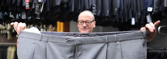 Unerwartet große Nachfrage: In einem Herrenausstatter in Hamburg zeigt ein Verkäufer die größte Hose im Sortiment.