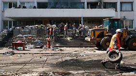 Arbeiter entfernen Barrikaden vor dem Rathaus von Mariupol.