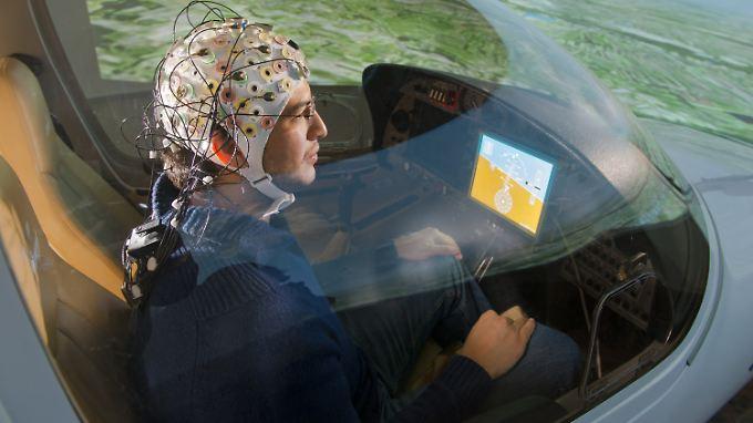 Guillermo Falconi sitzt am Lehrstuhl für Flugsystemdynamik in Garching bei München mit einer EEG-Kappe im Flugsimulator zum hirngesteuerten Fliegen.