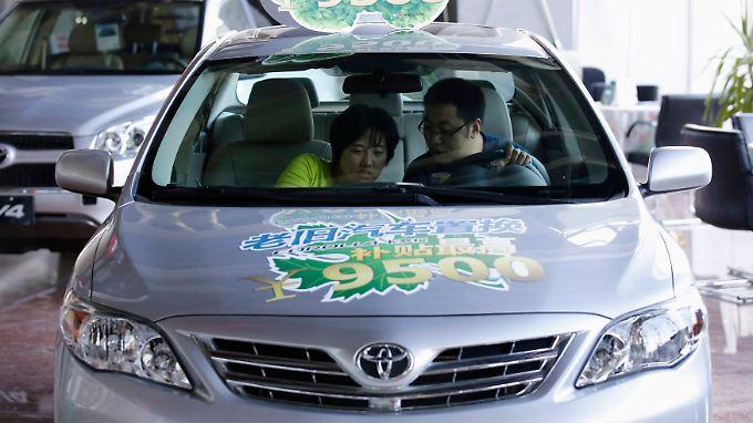 Mängel unterm Armaturenbrett: Ein Paar begutachtet bei einem Händler in Peking die Ausstattung eines Toyota Corolla (Archivbild).