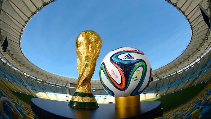 """""""Brazuca"""" (r), der Spielball für die Fußball-WM 2014 in Brasilien, liegt neben dem FIFA-WM-Pokal."""