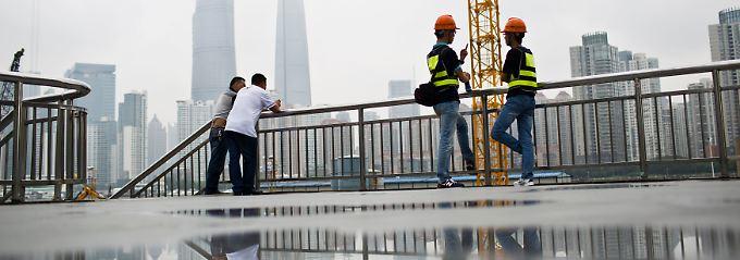 Später Juni in Shanghai: Unweit des Pudong-Viertels unterhalten sich Arbeiter und Angestellte über die aktuellen Börsengänge.