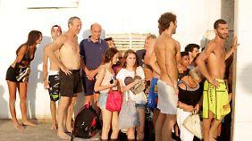 In Tel Aviv suchen Urlauber Schutz an einer Hotelwand, nachdem der Luftalarm ausgelöst wurde.