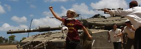 Ultraorthodoxe Juden stehen an einem israelischen Panzer an der Grenze zwischen Israel und dem Gazastreifen.