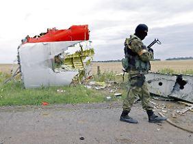 Schwer bewaffnete Separatisten vor einem Trümmerteil der abgestürzten Maschine.