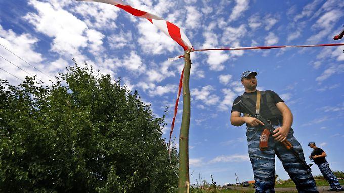 Separatisten stehen an der Absturzstelle von Flug MH17.
