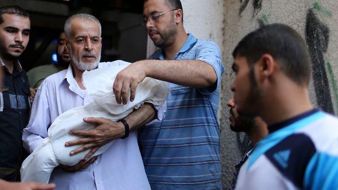 Ein Verwandter der Familie Deif präsentiert der Öffentlichkeit die Leiche des getöteten Kindes.
