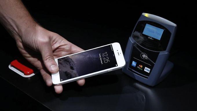 Bei Apple Pay wird iPhone an das Lesegerät gehalten und die Zahlung per Fingerabdruck auf dem iPhone-Sensor bestätigt.