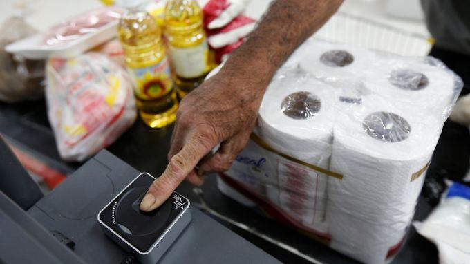 Ein Kunde lässt seinen Fingerabdruck an der Kasse eines staatlichen Supermarktes einscannen. Grund für die Maßnahme sind befürchtete Hamsterkäufe durch verzweifelte Venezuelaner.