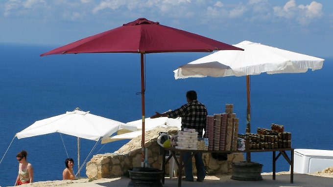 An der Westküste der griechischen Insel Zakynthos bietet ein Händler Touristen seine Waren an.