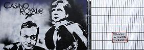 Ein altes Graffity vom Sommer 2013 am Bauzaun des heutigen EZB-Sitzes in Frankfurt. Bundeskanzlerin Angela Merkel ist gegen eine Vergemeinschaftung der Risiken in der Eurozone.