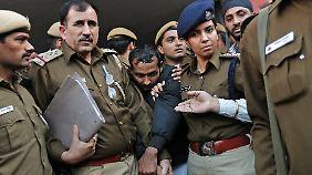 Der Fahrer, der wegen Vergewaltigung inzwischen vor Gericht steht, wird von Sicherheitsleute eskortiert.