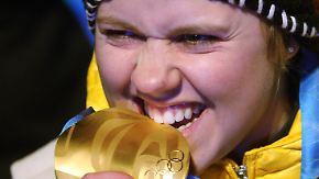 Klassische Sportlergeste: Ob die kanadische Olympiamedaille gut schmeckt?