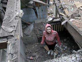 Eine junge Frau steht in Donezk in ihrem zerstörten Haus.