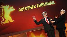 Wim Wenders (l.) ist begeistert, als ihm Berlinale-Direktor Dieter Kosslick den Goldenen Ehrenbären überreicht.