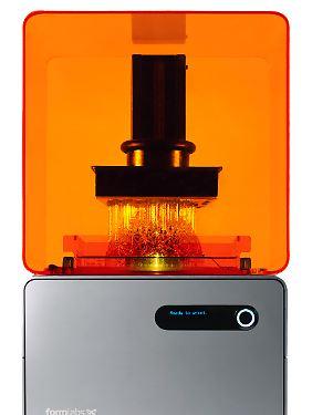 Stereolithographie bei der Arbeit: Der Laser wirkt von unten, ein Hubarm zieht das Objekt in Mikrometerschritten aus dem Harzfilm heraus.