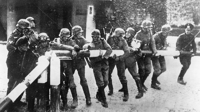 1. September 1939: Soldaten der deutschen Wehrmacht reißen an der deutsch-polnischen Grenze einen Schlagbaum nieder.
