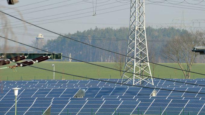 Ein Strommast des 50 Hertz Transmission Control Center in Neuenhagen (Brandenburg) zwischen Solaranlagen. Der Übertragungsnetzbetreiber musste die zu erwartenden Spannungsverluste durch die Sonnenfinsternis ausgleichen.