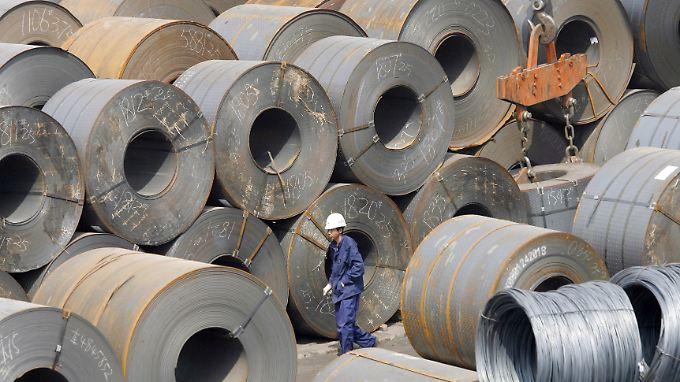 Ein Arbeiter inmitten von Stahlrollen auf einem Verladeplatz in Shenyang in China.