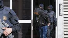 Spanische Polizeibeamte führen einen der Verdächtigen nach der Stürmung des Gebäudes nordöstlich von Barcelona ab.