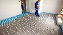 Bei der Installation einer Fußbodenheizung werden Schläuche mit Hilfe eines Tackers auf Dämmplatten verlegt, darüber kommt Estrich. Foto: Nestor Bachmann