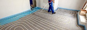 Bei der Installation einer Fußbodenheizung werden Schläuche mit Hilfe eines Tackers auf Dämmplatten verlegt, darüber kommt Estrich.