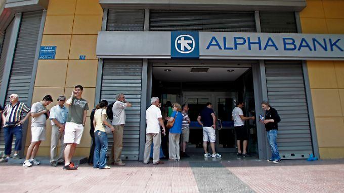 Kunden stehen am Geldautomaten einer griechischen Bank an.